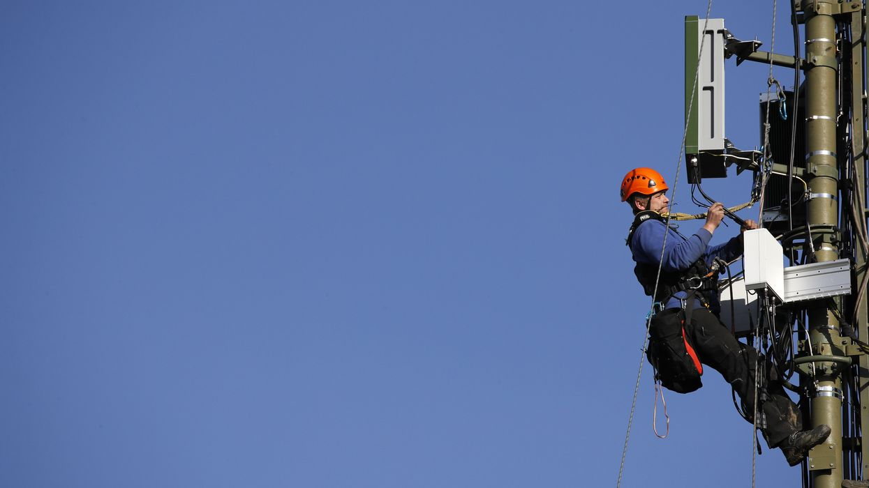 An engineer installing a 5G station on a cell tower.