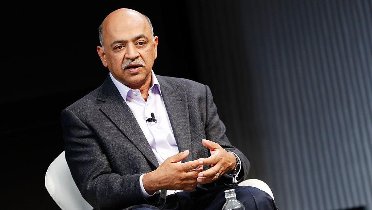 IBM CEO Arvind Krishna speaks while seated in front of an open water bottle.