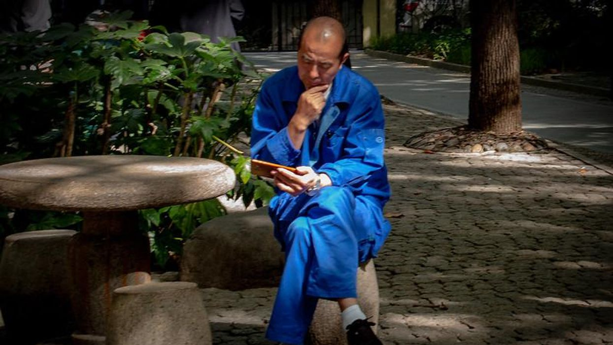 An older man looks at his phone while relaxing in People's Park in Shanghai.
