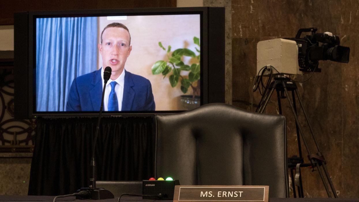 Facebook CEO Mark Zuckerberg appears on a screen behind a lawmaker's empty chair as he testifies remotely during Senate hearing.
