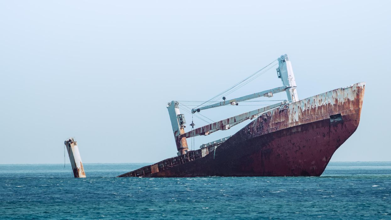 A rusty ship sinking in the ocean, one end already underwater.