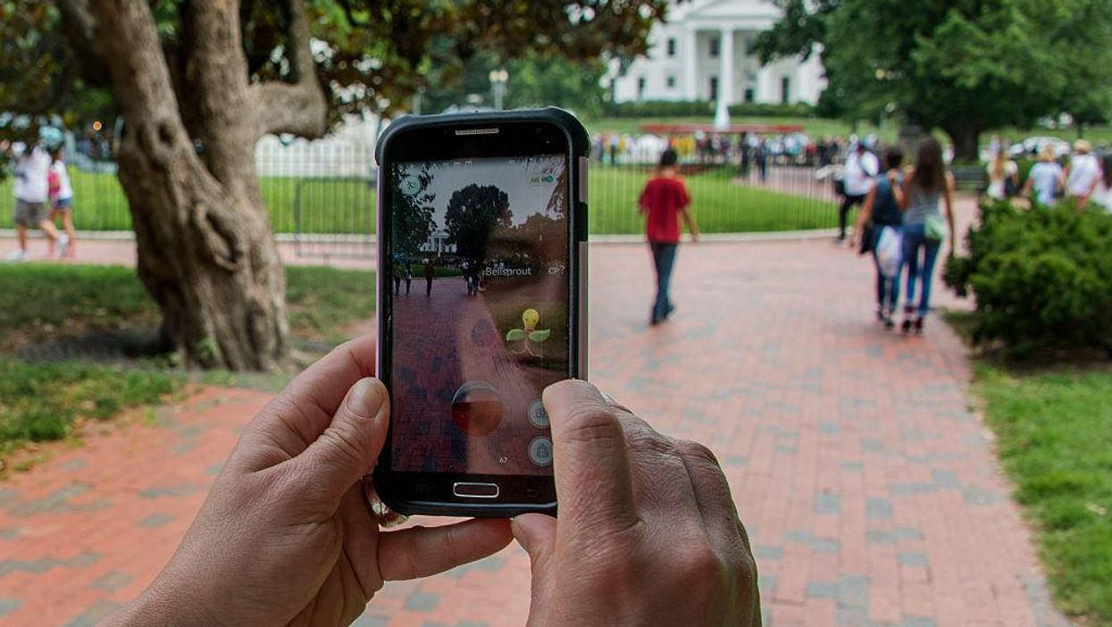 A woman holds up her cell phone as she plays the Pokemon Go game in Lafayette Park in front of the White House in Washington, DC, July 12, 2016.