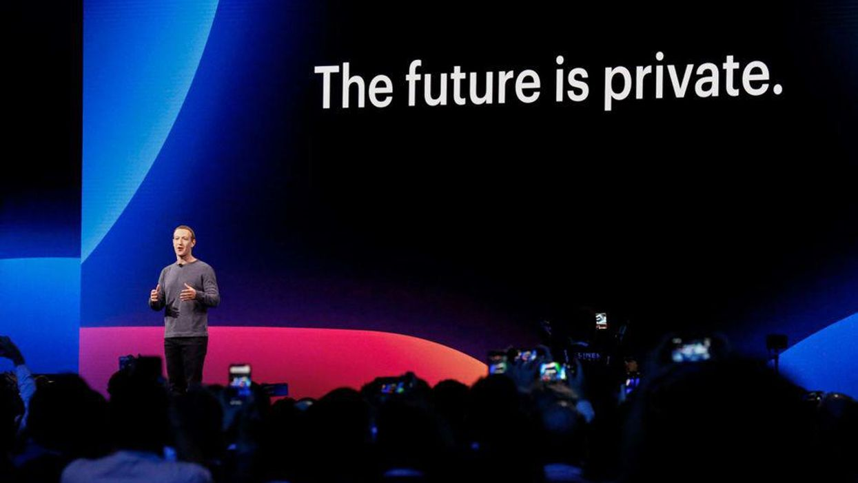 """As onlookers take photos on their phones, Facebook CEO Mark Zuckerberg speaks before a screen that says, """"The future is private."""""""