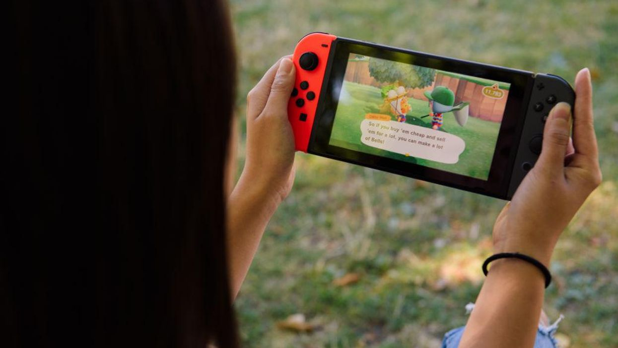 A close-up of two hands holding a Nintendo Switch, which is running Animal Crossing: New Horizons.