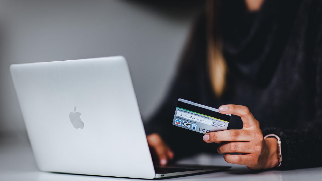 Person holds credit card in front of laptop