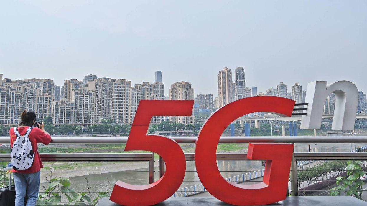CHONGQING, CHINA - MAY 10: A woman stands beside a China Unicom 5G sign on May 10, 2021 in Chongqing, China.