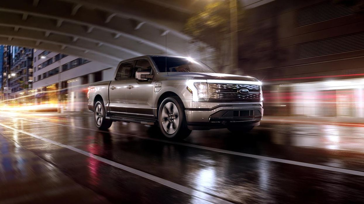 An electric F-150 Lightning truck driving through a moodily-lit underpass.