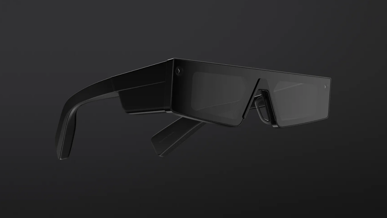 A pair of black, square-edged augmented reality glasses against a black gradient background