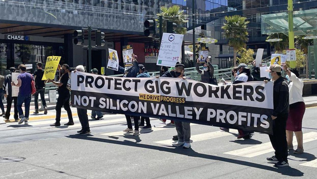 Gig workers hold a sign in a crosswalk outside Uber headquarters in San Francisco.