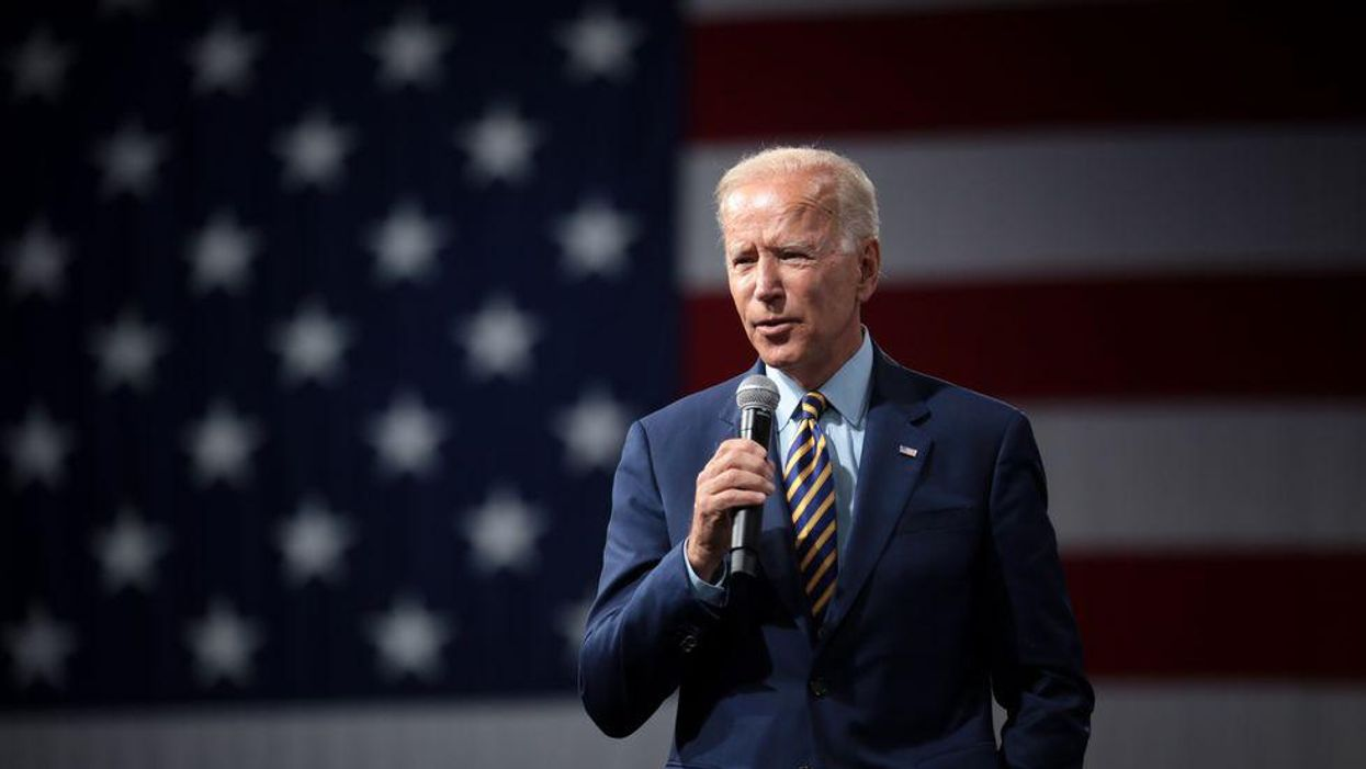 President Joe Biden speaking into a handheld microphone in front of an American flag backdrop