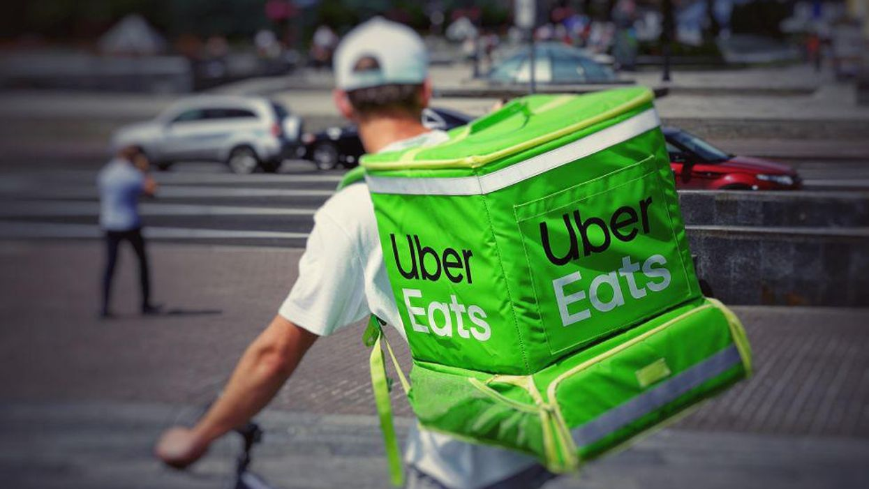 A gig worker rides with an Uber Eats backpack.