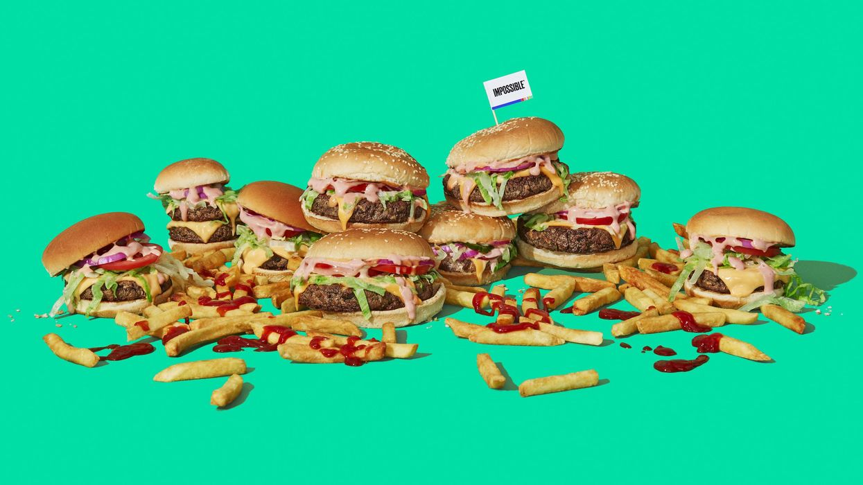 A pile of burgers and fries doused in ketchup on a green background