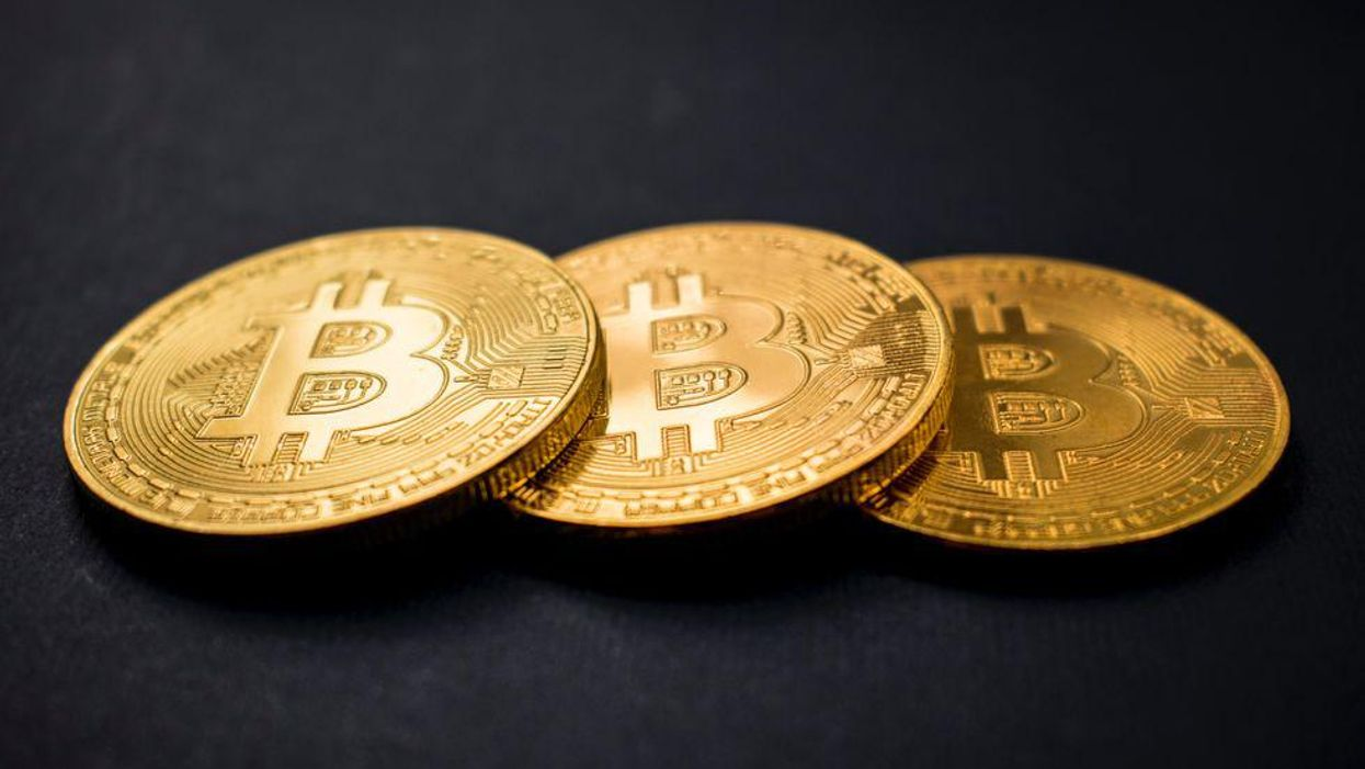 three gold-colored bitcoins on black surface