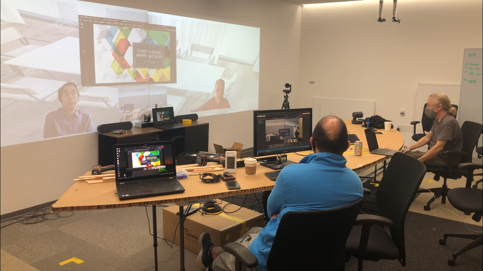 Microsoft workers at a curved desk looking at their remote colleagues projected on screen