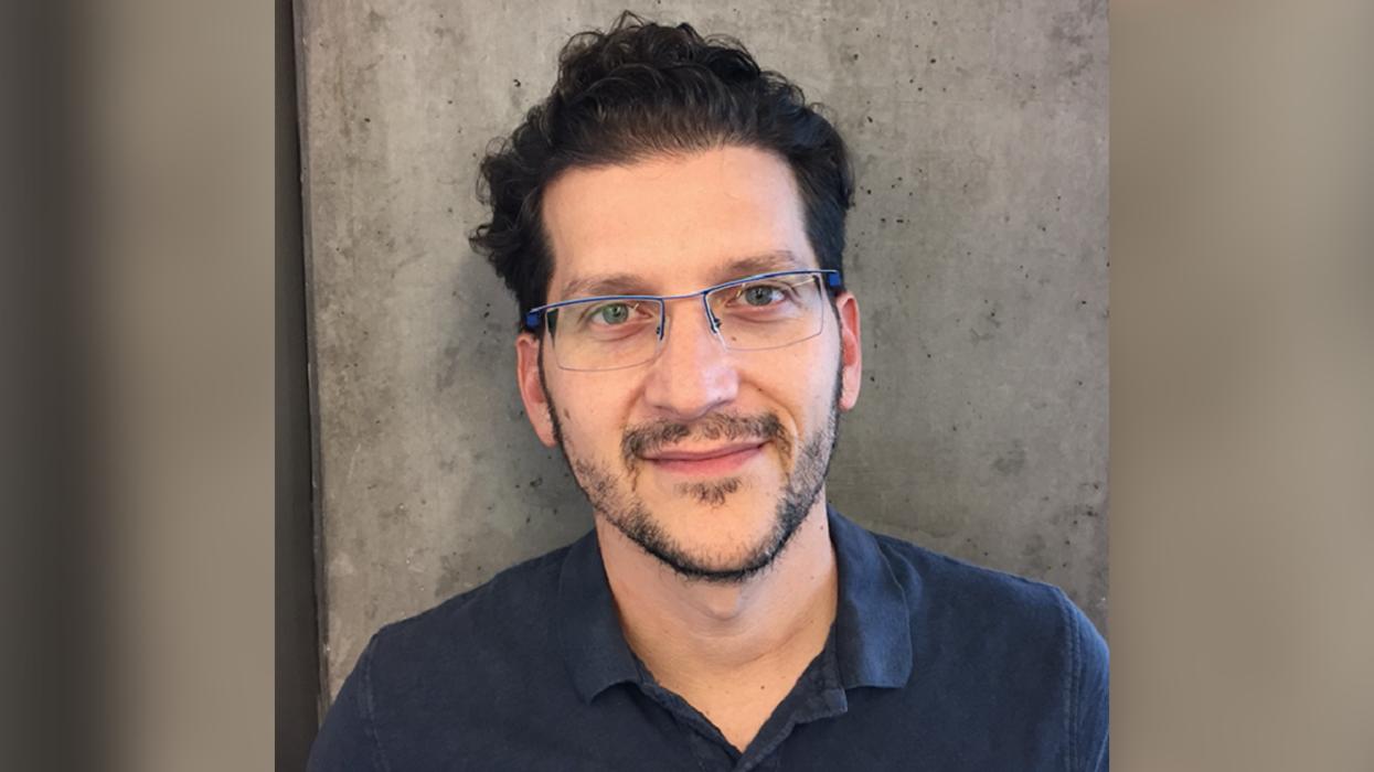 Daniel Rausch, wearing glasses, standing against a wall wearing a blue shirt
