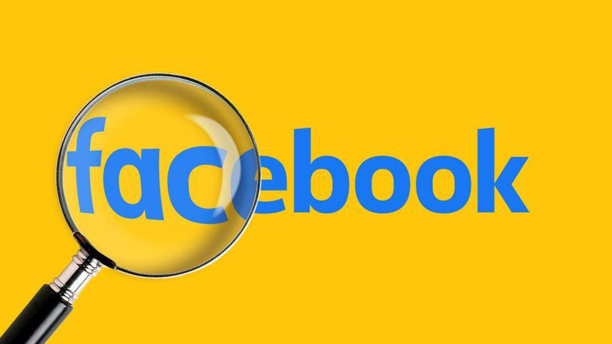 A magnifying glass enlarges part of the Facebook logo.