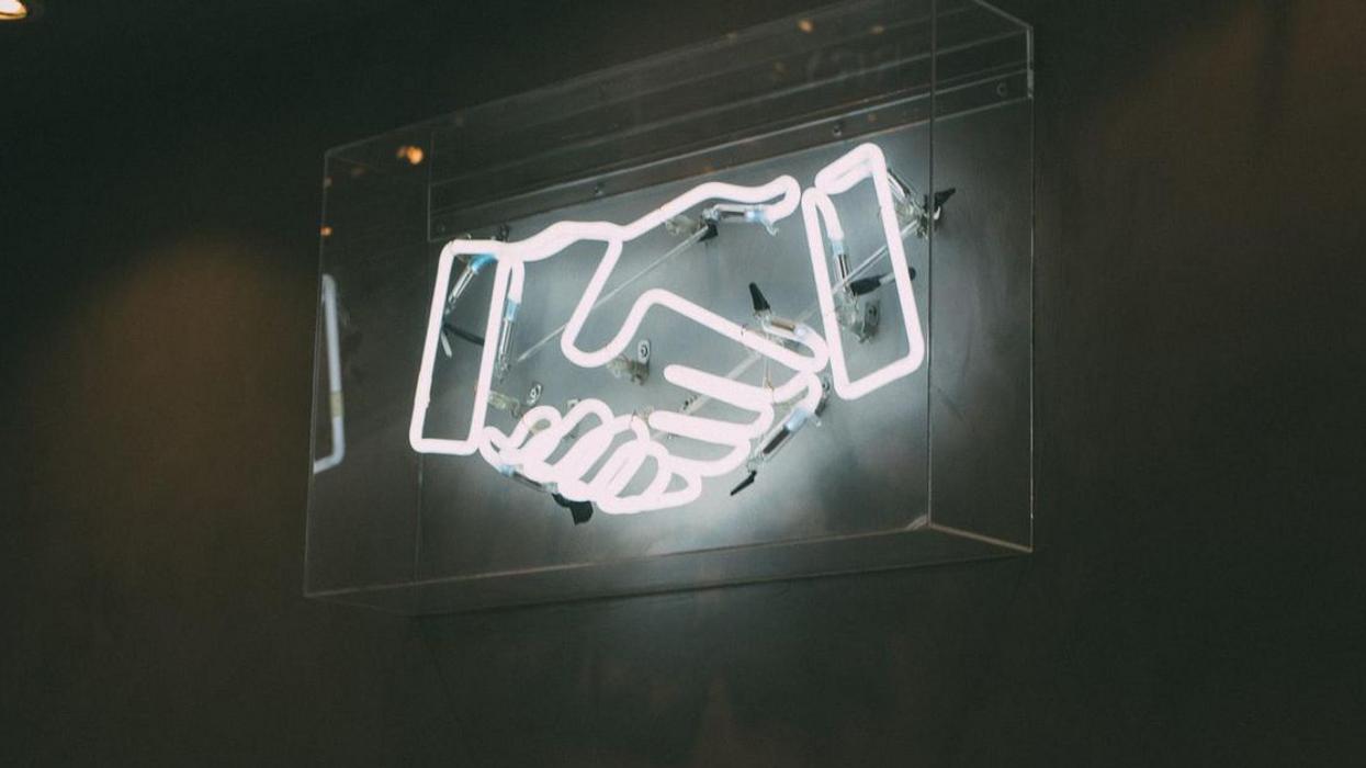 Two neon digital hands shaking