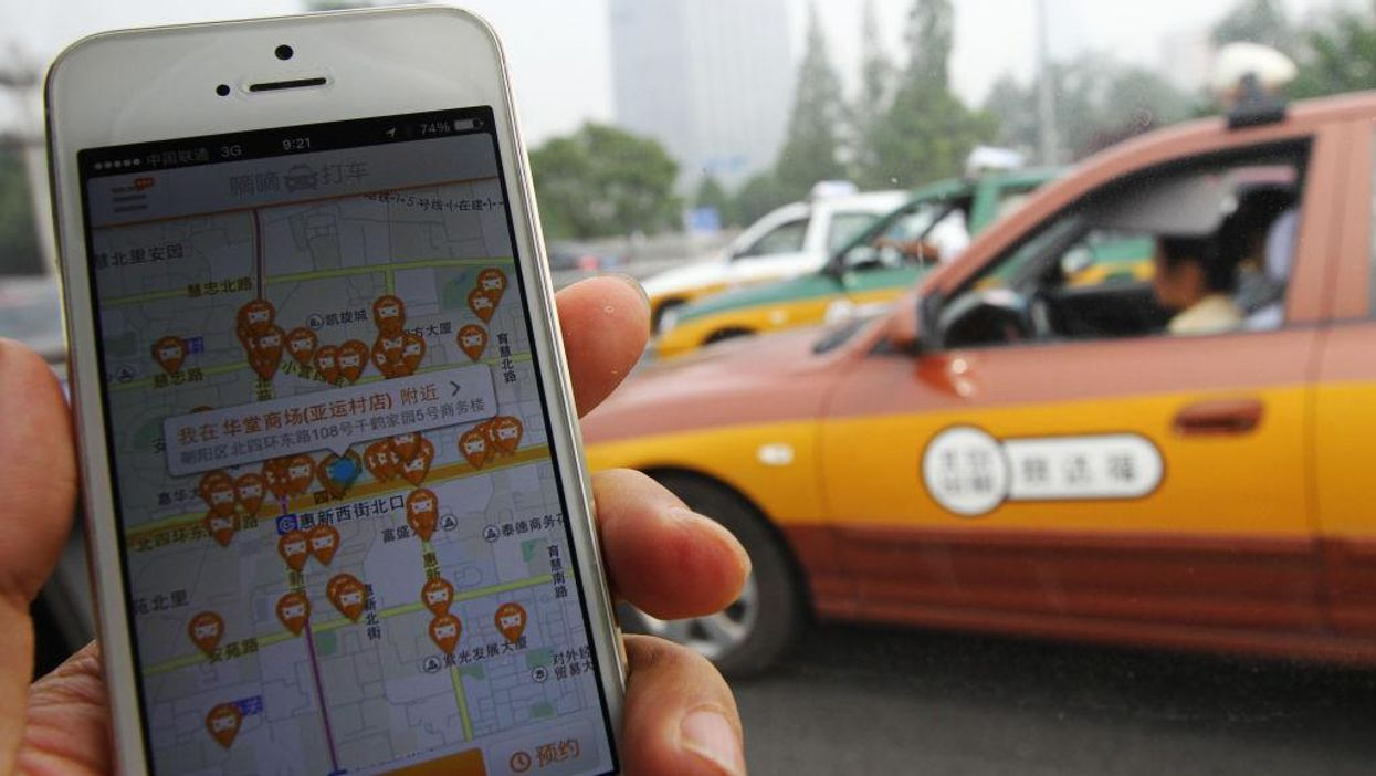 Phone showing the DiDi app in use with a car in the background.