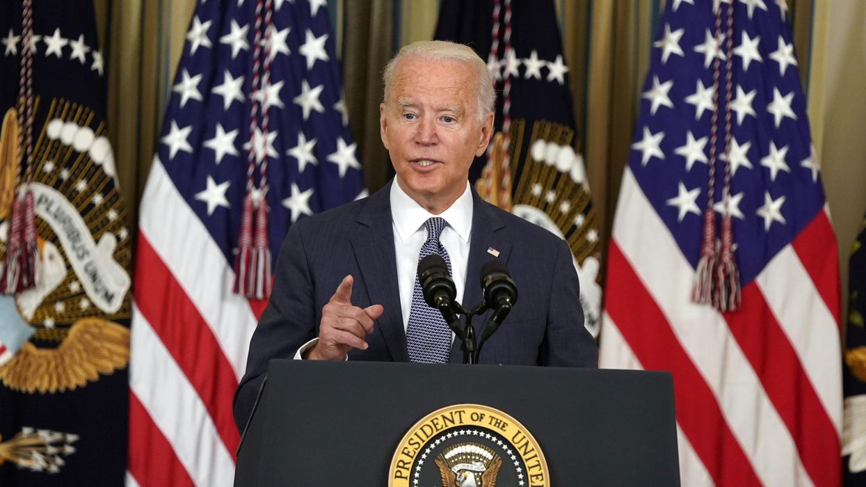 President Joe Biden speaking at a podium, flanked by US flags