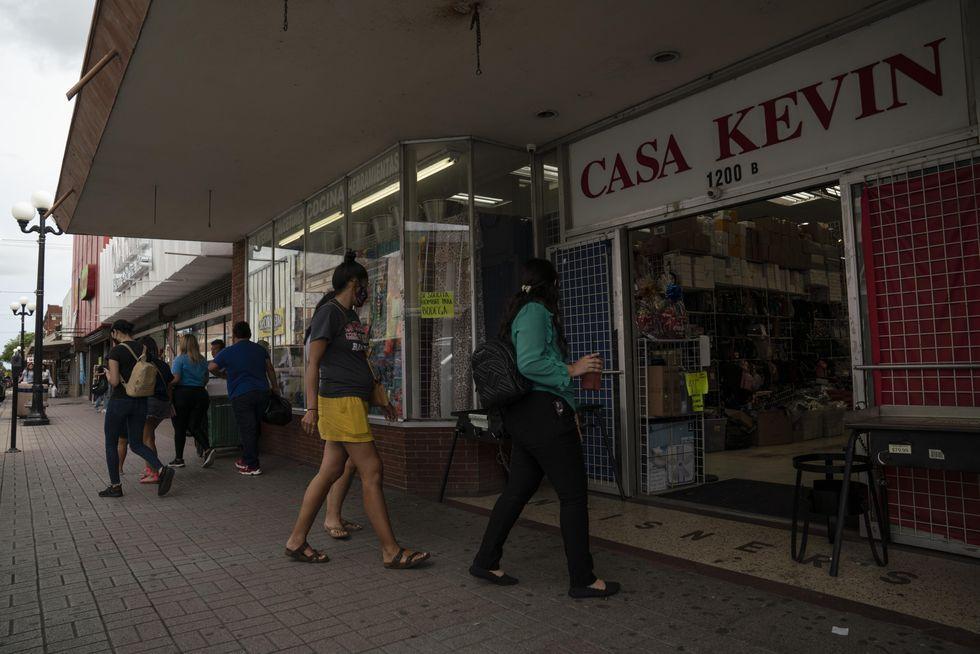 People walk by businesses on Elizabeth Street in Brownsville, Texas.