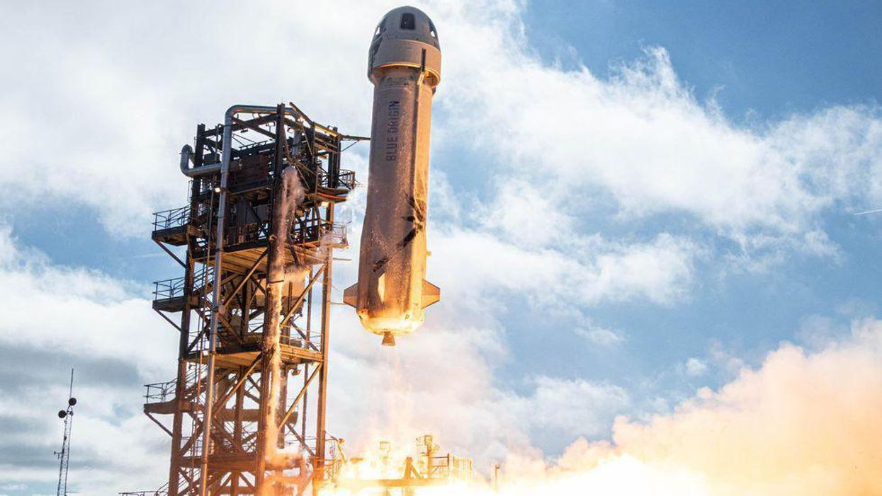 A Blue Origin rocket begins to take off.