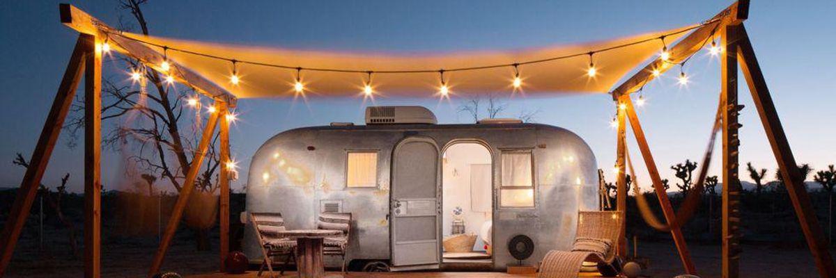 A vintage trailer in a desert under string lights.