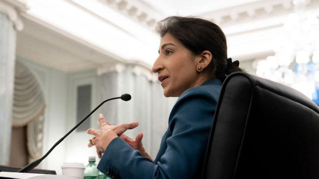 FTC chair Lina Khan speaks into a microphone.