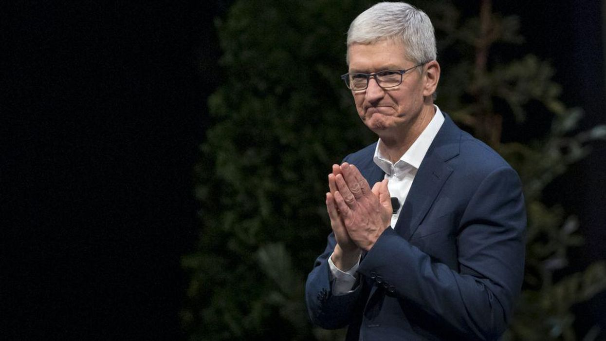 Apple CEO Tim Cook holds his hands together in front of his chest.