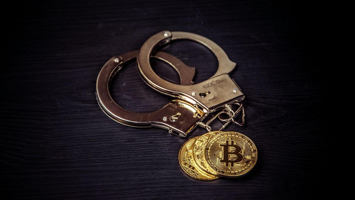 Handcuffs next to bitcoins