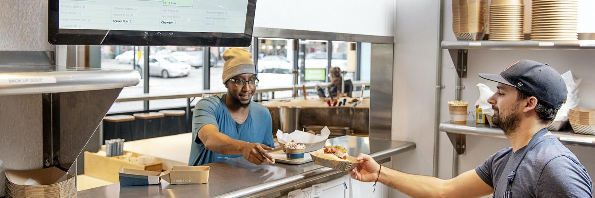 Kitchen worker passes food to customer