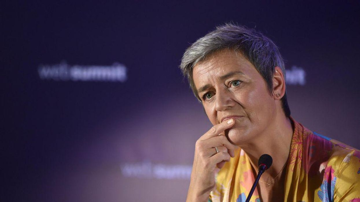 Margrethe Vestager holds her hand to her face during an event.