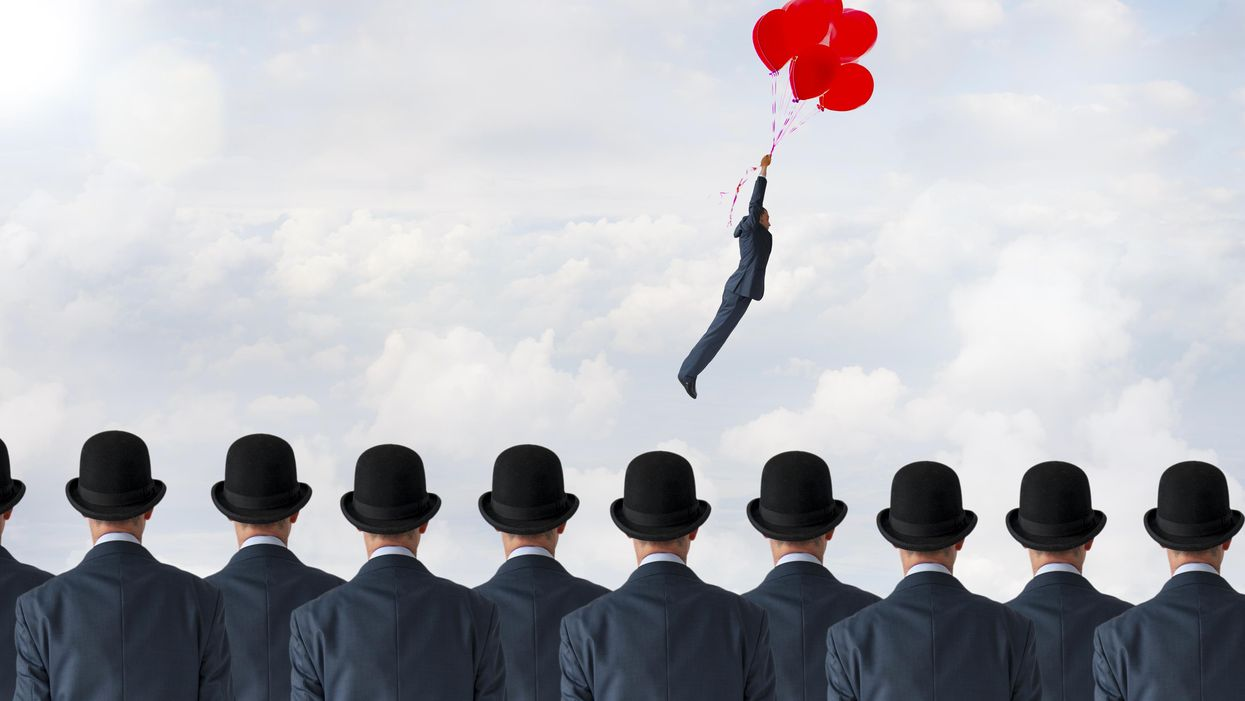 One man with balloons flies above men in hats