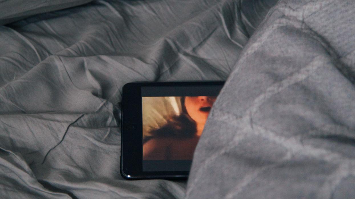 A smartphone on a gray bedsheet