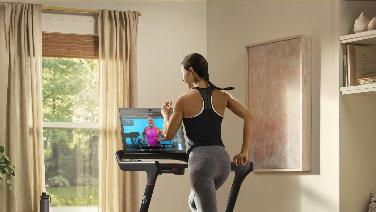 A woman using a Peloton treadmill, which is displaying an instructor on the attached monitor.