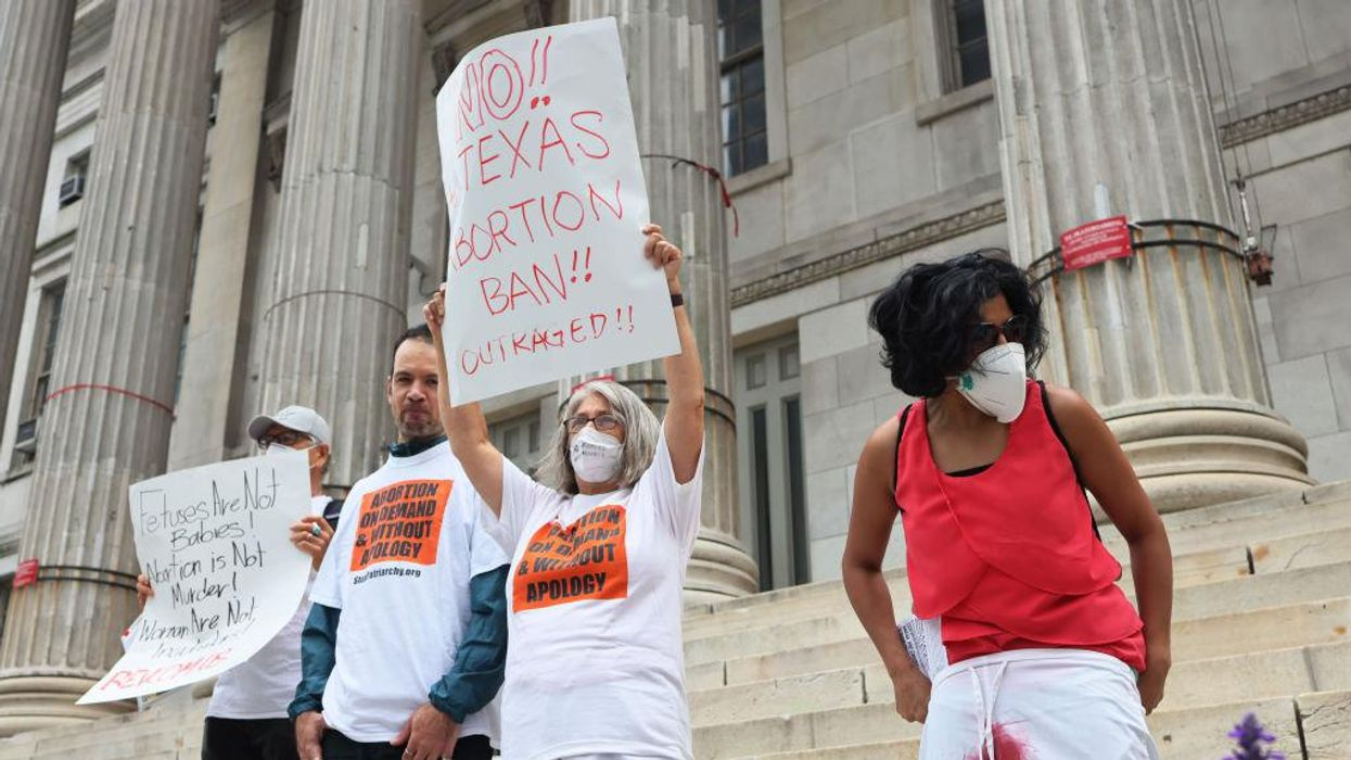 Protestors stand at a reproductive rights rally