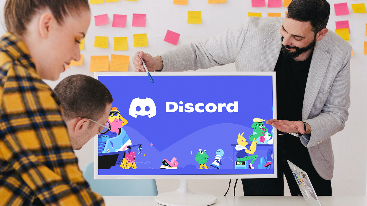 People surrounding an office computer with Discord's logo.