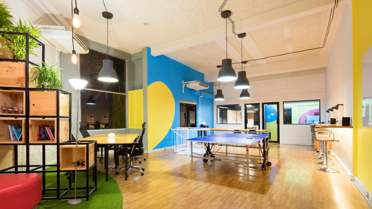 A startup-looking office with a ping-pong table in the middle of the floor.