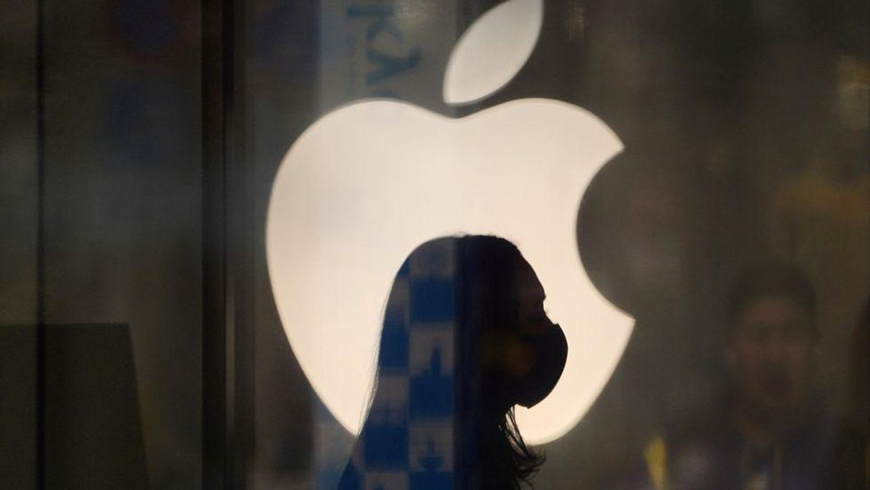 Person wearing a mask walks in front of Apple logo