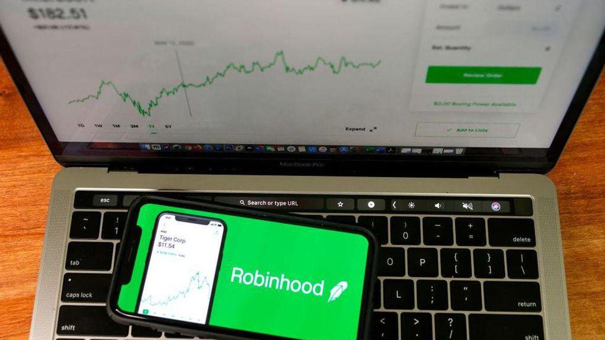 Phone with Robinhood app open on top of open laptop's keyboard