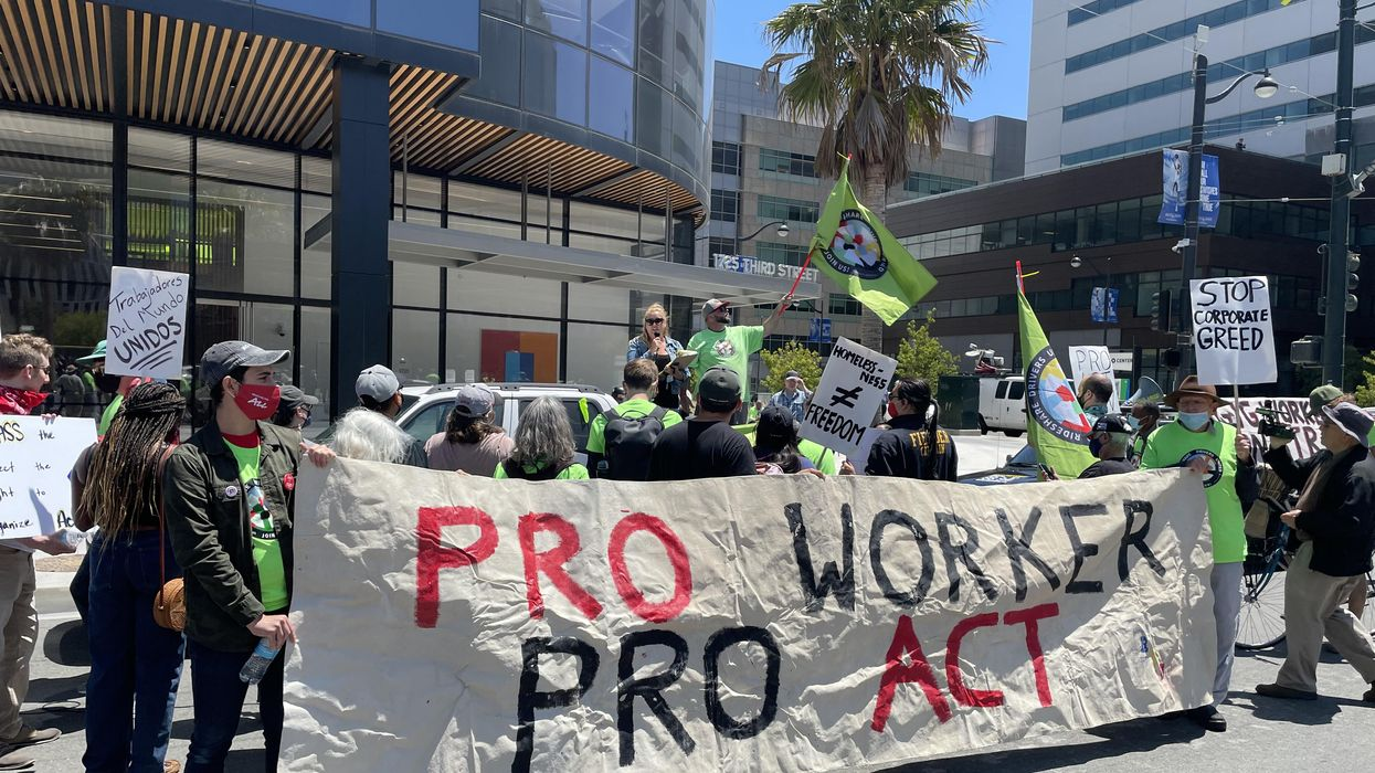 Rideshare drivers and supporters rally at an Uber office in San Francisco