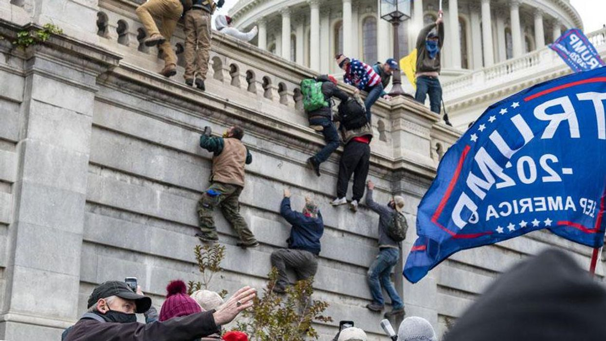 Rioters scaling the U.S. Capitol walls during the insurrection