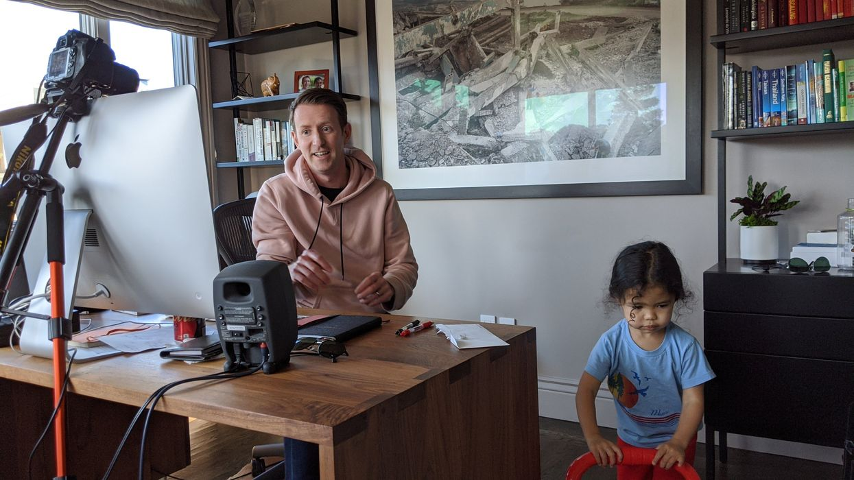Rippling COO Matt MacInnis at his desk, with his child nearby