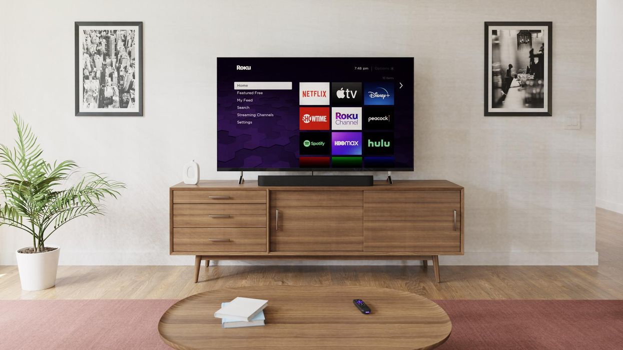 A TV sitting on a credenza with Roku's interface on the screen.