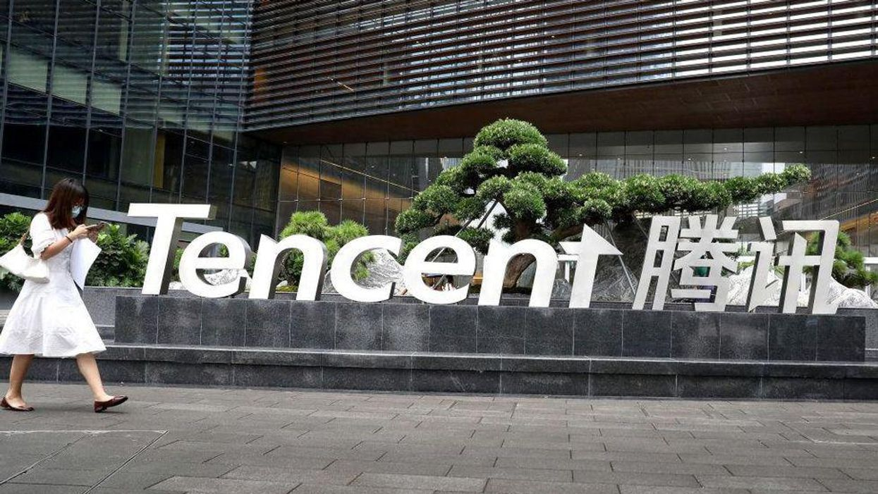 A woman walks outside the headquarters of Tencent while looking at her phone.