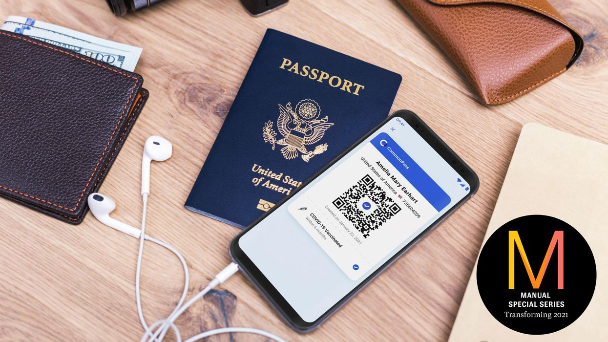 Smartphone with a vaccine passport on a table with a regular passport and a wallet