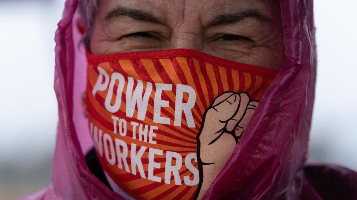 """A demonstrator wears a protective mask that reads """"Power To The Workers"""""""