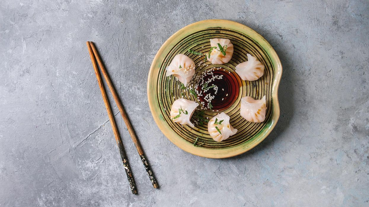 Steamed potstickers dumplings stuffed by shrimps, served on ceramic plate with soy sesame sauce.