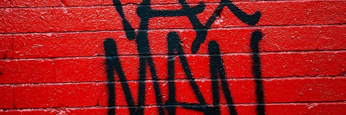 """""""Tax man"""" graffiti on a red wall"""