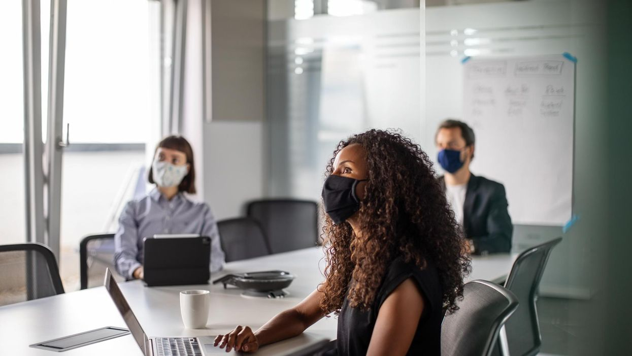 Masked people sitting at a conference table