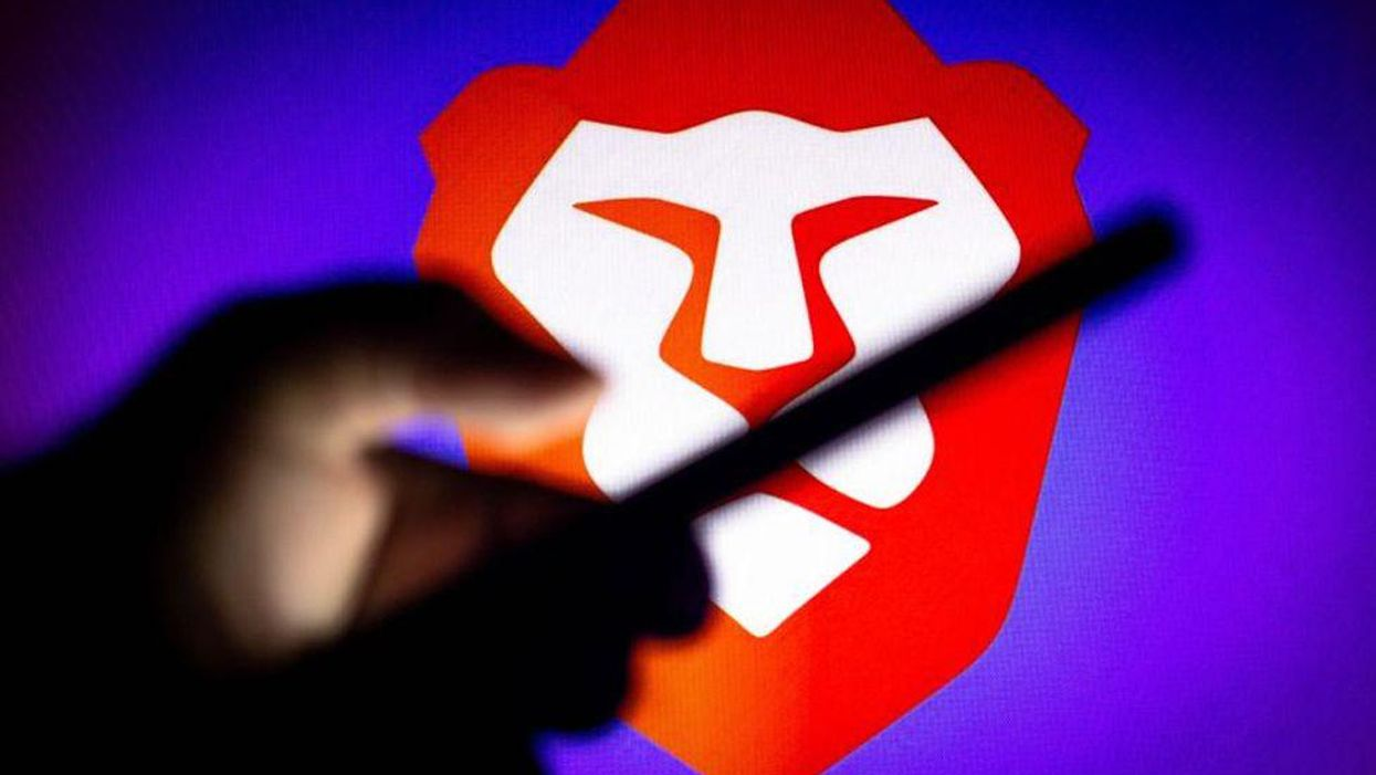 """The brave """"lion"""" logo displayed behing the silhouette of a hand holding a smartphone"""